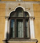 Three-cusped arched Neo-Romanian style house window framed by columns with carved capitals, Bucharest